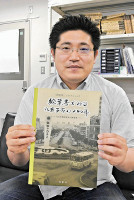 出版した写真資料集を手にする村松さん.jpg